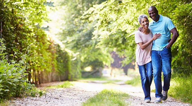 couple walking for exercise on gravel path