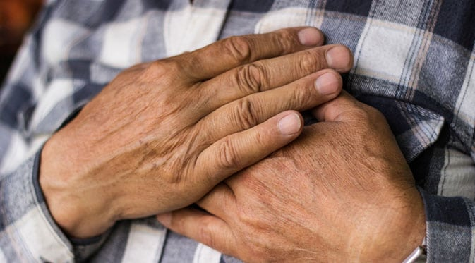 male hands holding chest over heart