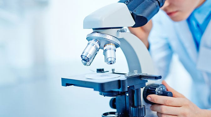 technician looking through microscope