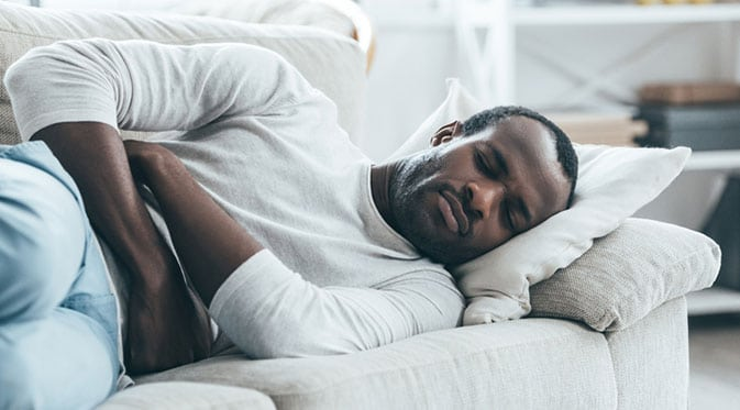 man laying on couch holding stomach